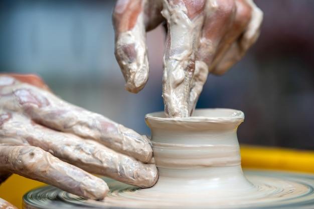 도예가의 손으로 물레로 도자기 접시를 만든다