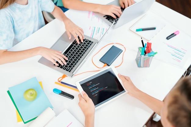 Руки трех умных школьников с современными мобильными гаджетами за столом во время работы в сети или подготовки домашнего задания