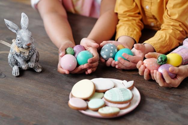 Руки трех межкультурных маленьких детей в повседневной одежде с крашеными пасхальными яйцами среди печенья и игрушечного кролика, сидя за столом