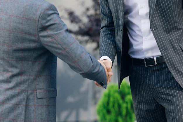 ビジネススーツのトップマネージャーの手は、ビジネスセンターの背景で互いに握手します。契約に同意するか、挨拶します。認識できない人。