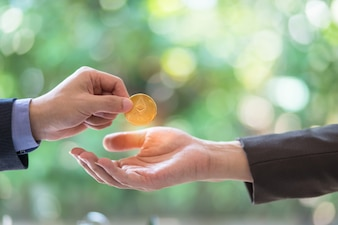 Hands of two businessman are trading coin of ethereum.