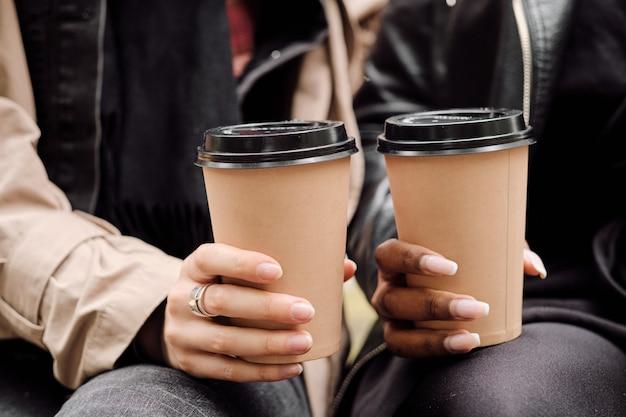 飲み物を持っている2人の異文化間の女性の手