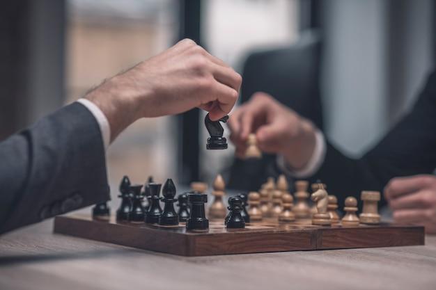 Руки двух игроков одновременно над шахматной доской с шахматными фигурами в неосвещенной комнате