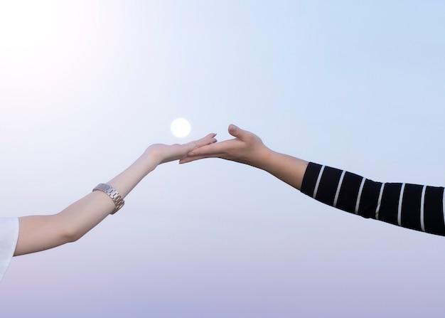 Руки двух женщин пара с луной в стене