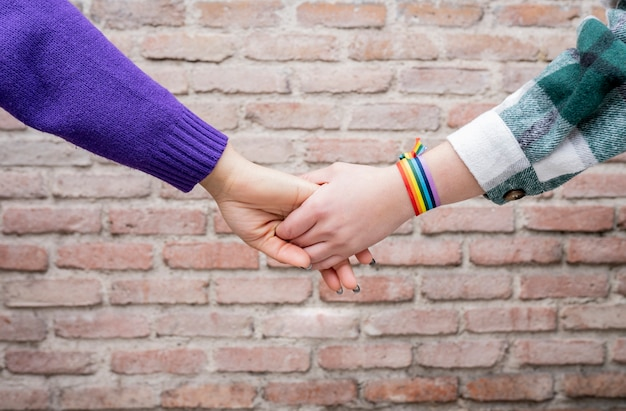 レインボーアームバンドゲイプライドを持つ2人の女性の手