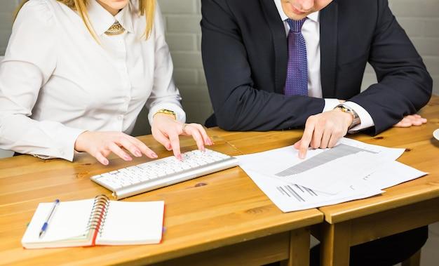 現代的なオフィスのクローズアップのテーブルで働く2人の若いビジネスマンの手。