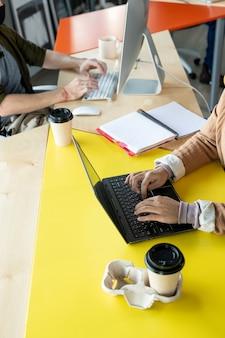 Руки двух молодых сотрудников в повседневной одежде, сидящих за столом и нажимающих кнопки компьютерных клавиатур во время индивидуальной работы в офисе