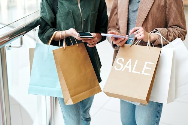 온라인 상품을 스크롤하고 가격을 비교하는 스마트 폰과 종이 봉투를 들고있는 두 명의 젊은 현대 쇼핑객의 손