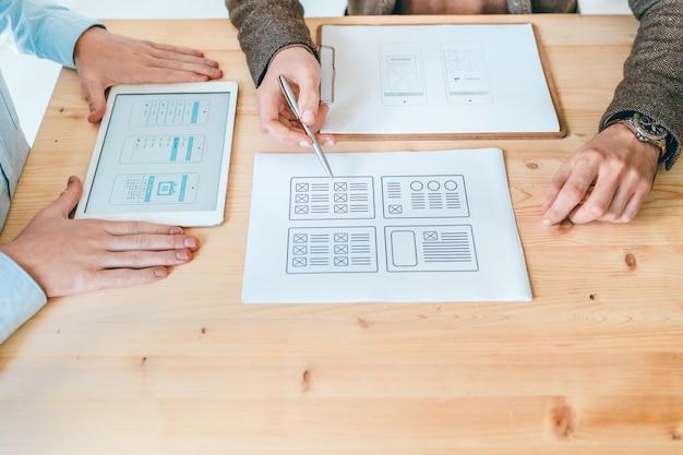 Руки двух молодых дизайнеров обсуждают макеты новых веб-сайтов на бумаге и сенсорной панели