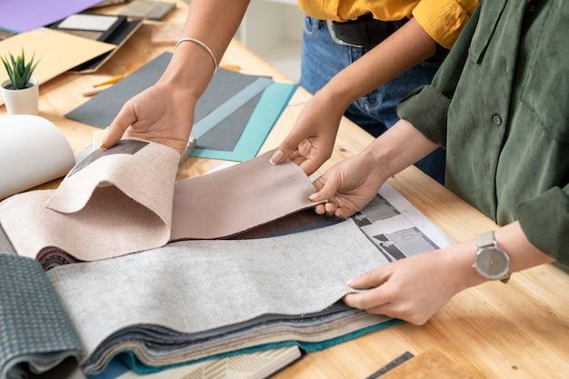 Руки двух молодых коллег-женщин просматривают образцы тканей у стола, выбирая подходящие для современной мебели