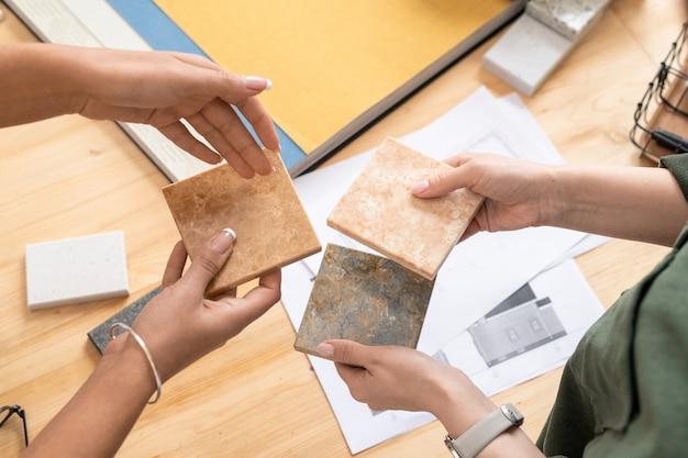 Руки двух молодых дизайнеров женского пола сравнивают образцы мраморной плитки