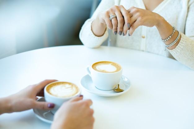 休憩中の会話中にカプチーノをしながらカフェのテーブルのそばに座っているカジュアルウェアの2人の若いフレンドリーな女性の手