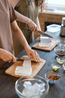 Руки двух молодых женщин, нарезающих твердую мыльную массу кубиками на досках, стоя у стола с ингредиентами для изготовления косметических продуктов
