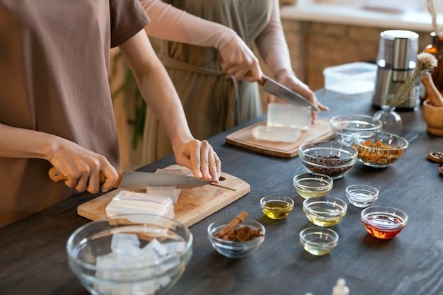 自宅で自然化粧品を作る前に、硬い石鹸の塊を木の板で立方体に切る2人の若い女性の手