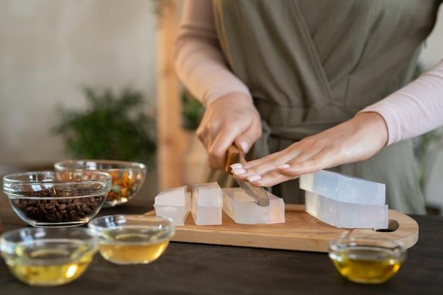 Руки двух молодых женщин режут твердую мыльную массу кубиками на деревянных досках перед тем, как делать натуральные косметические продукты в домашних условиях