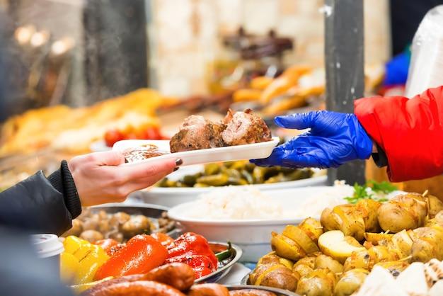 길거리 음식 시장에서 음식을 제공하는 공급업체의 손