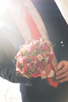 スーツの準備をしている結婚式の新郎の手。新郎はウェディングブーケを持っています。