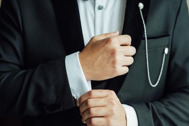 スーツで準備をしている結婚式の新郎の手