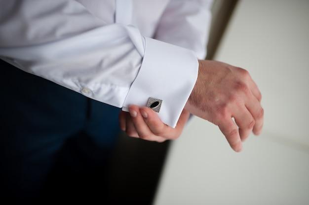 Руки жениха готовятся в костюме