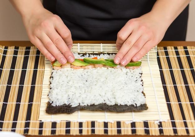 Руки повара женщины закатывают японские суши