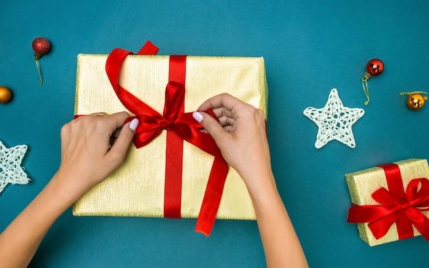 Руки женщины украшая рождественскую подарочную коробку.