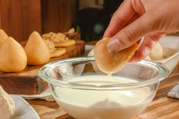 Руки женщины окунают бразильский крокет в молоко