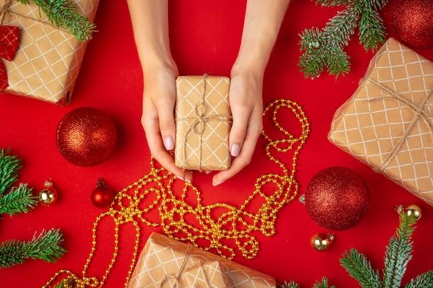 빨간색 배경에 크리스마스 선물 상자를 들고 있는 여성의 손