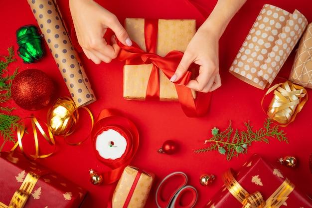 Руки женщины, держащей рождественскую подарочную коробку на красном фоне