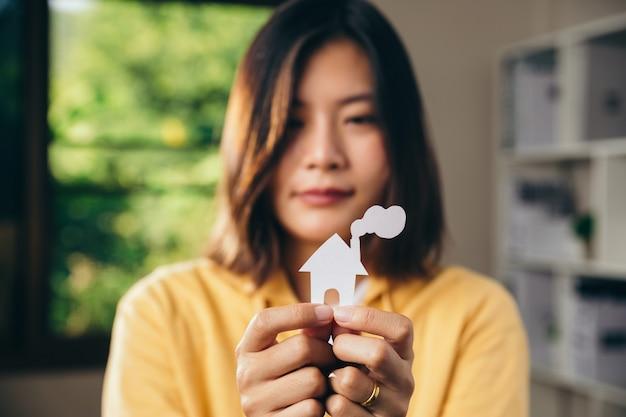 リビングルームで切り抜き紙ごみを家に持っている女性の手、保護の概念。