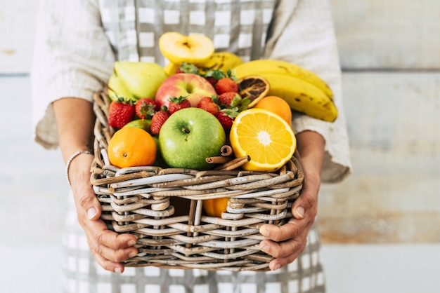 다채로운 혼합 과일이 가득한 고리버들 바구니를 들고 있는 여성의 손. 바구니에 다양 한 건강 한 과일을 가진 여자입니다. 체중 감량 또는 건강한 식생활을 위한 신선한 과일 수집