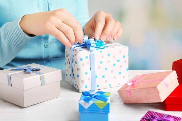 Руки женщины, упаковывающие подарки к празднику