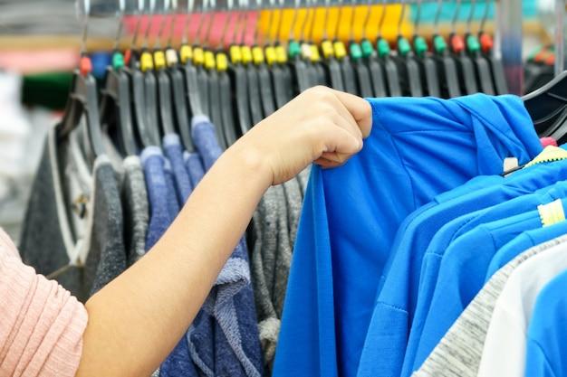 Руки женщины, выбирая голубую одежду в модный магазин.