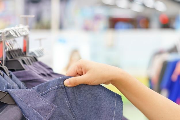 Руки женщины, выбирая джинсовую одежду в модный магазин.