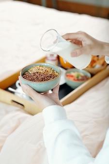 彼女が朝食のために持っているグラノーラのボウルに非乳製品のヨーグルトを注ぐ女性の手