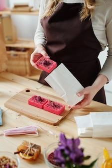 Руки женщины кладут кусок розового мыла ручной работы в пакет из белой бумаги над деревянным столом в мастерской