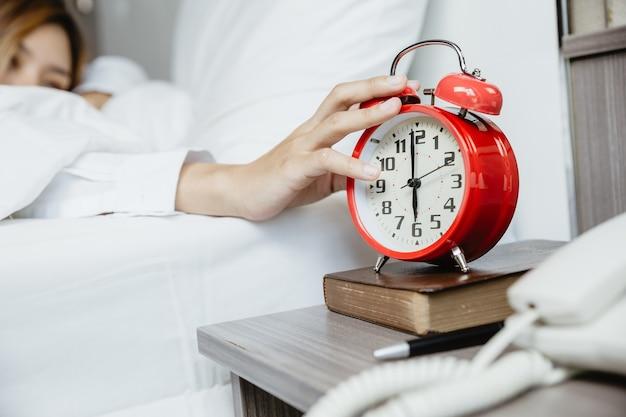 Руки женщины, протягивая руку, чтобы остановить будильник