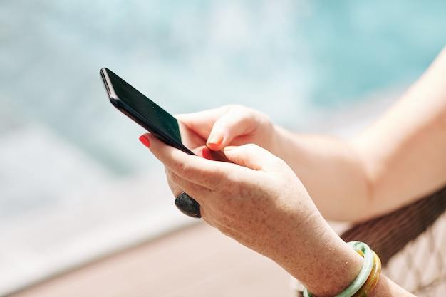 スイミングプールで休んでいる女性の手、テキストメッセージ、モバイルアプリケーションの使用
