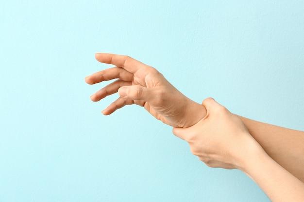 Руки женщины, страдающей синдромом паркинсона на цвете