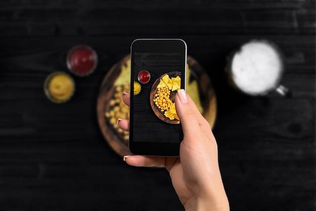 모바일 스마트 폰 탑 뷰 멕시코 나초로 음식 사진을 찍는 여성의 손