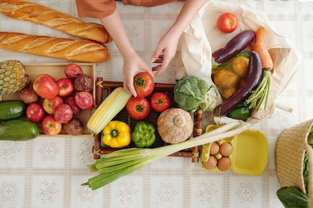 市場から帰ってきた後、台所のテーブルで果物や野菜のリサイクル可能なバッグを開梱する女性の手、上からの眺め