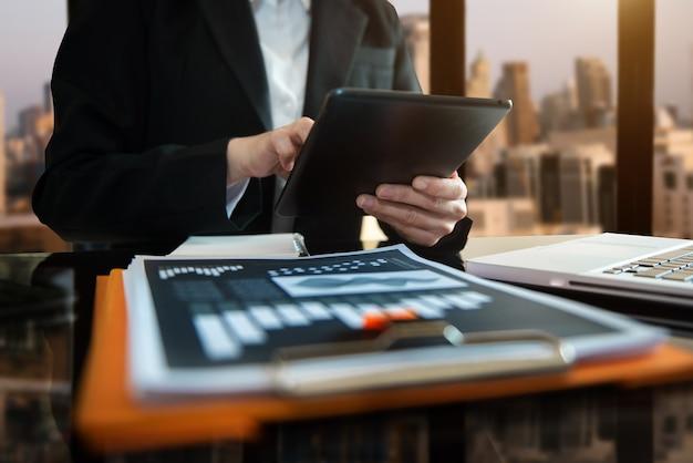 홈 오피스에서 노트북과 디지털 태블릿을 갖춘 현대적인 사무실에서 휴대전화를 사용하는 여성의 손