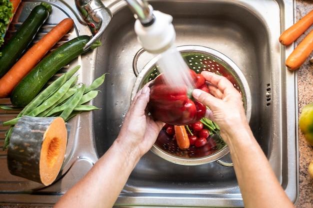 台所で野菜の新鮮な収穫を洗う女性の手は水のジェットの下に沈む
