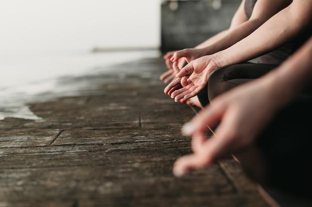 ヨガマットの上に座って海の近くに屋外瞑想する女性の手