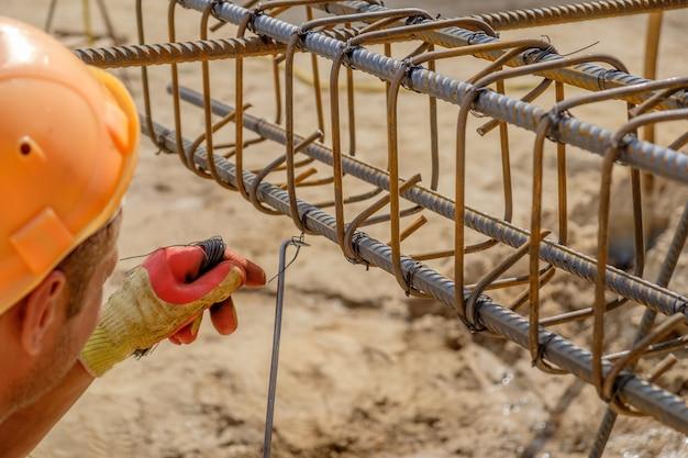 Руки работника в защитных перчатках связывают металлическими стержнями с проволокой для армирования бетона. вид крупным планом