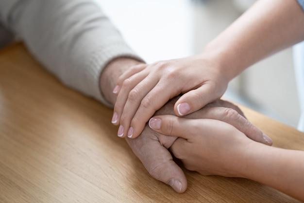 若い愛情のこもった手と木製のテーブルに彼女のシニアの父親のそれを保持している注意深い女性の手