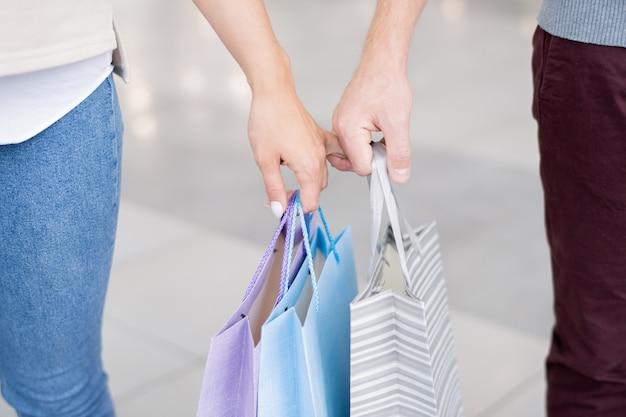 ショッピングの後、ショッピングモールを離れるときに紙袋を運んで指で保持している愛情のこもったカップルの手