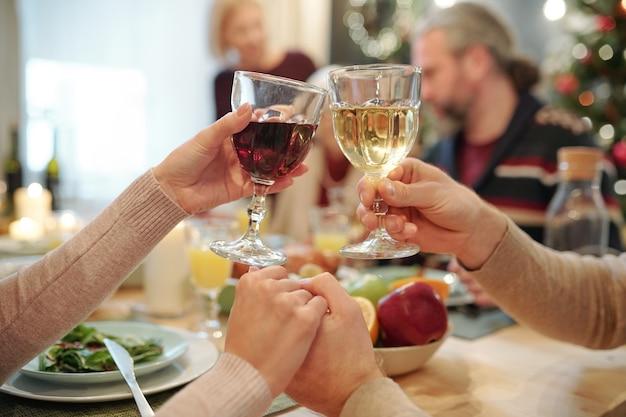 Руки молодой ласковой пары звенят бокалами вина после приготовления праздничного тоста за поданным столом на рождественском ужине