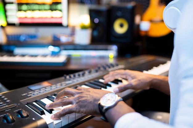 現代のサウンドレコーディングスタジオで一人で作業するピアノの鍵盤に若いアフリカ系アメリカ人ミュージシャンの手