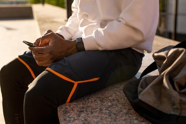 대리석 타일에 앉아 야외 훈련 후 휴식을 취하는 동안 스마트 폰이 온라인 뉴스를 통해 서핑하는 젊은 아프리카 남자의 손