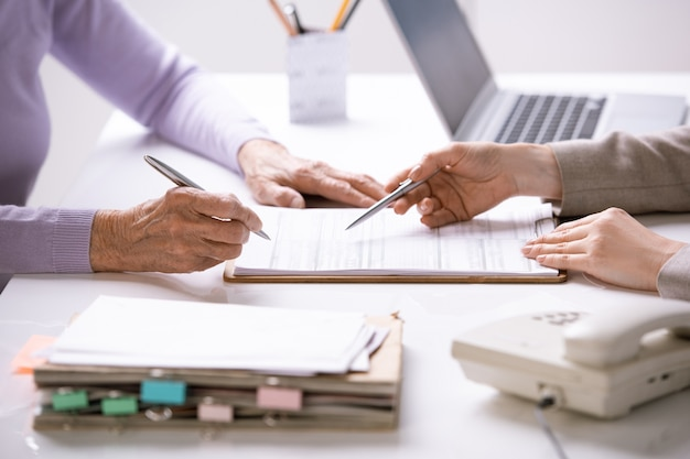 Руки молодого агента, указывающие на страховой документ, и руки старшего клиента-женщины, собирающегося поставить в нем свою подпись